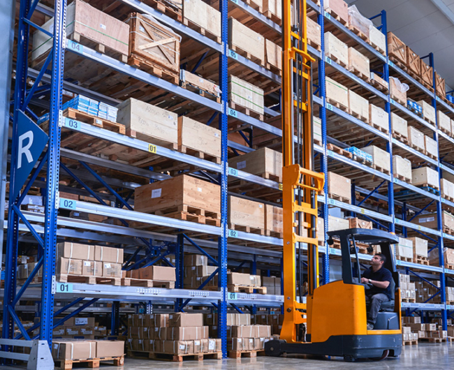 An orange forklift working next to a blue shelving system